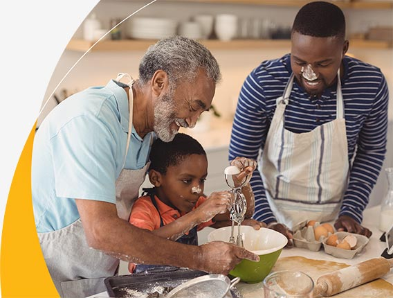 A young boy and his father and grandfather laugh together as they messily mix cake batter at the kitchen counter