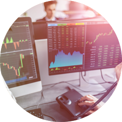 a broker looks at charts on computer screens