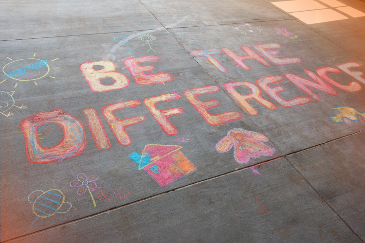 sidewalk chalk art reads 'be the difference'