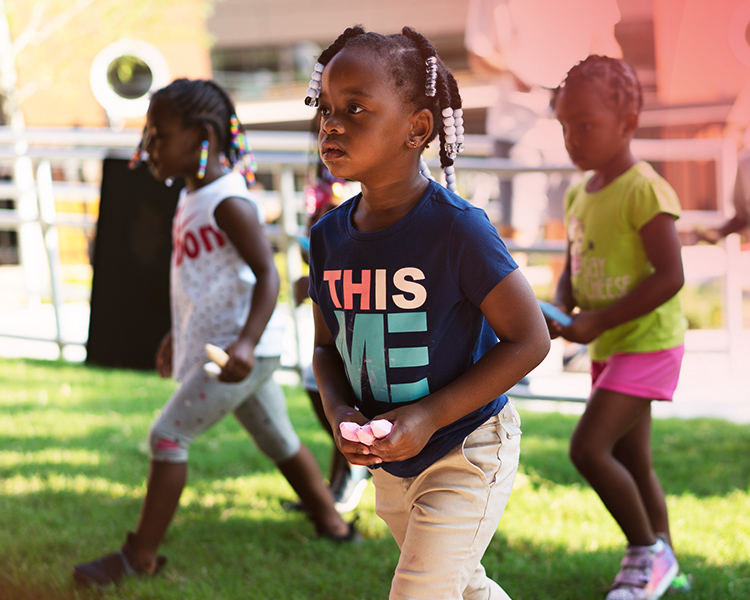 3 young girls play outdoors with chalk at the YMCA