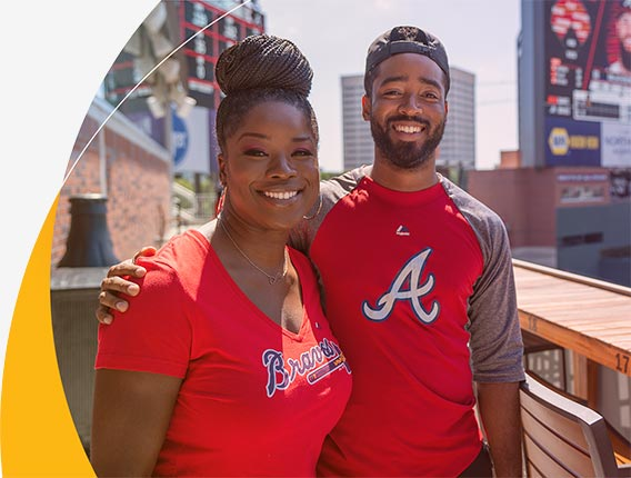 Two young Gas South employees wearing Atlanta Braves t-shirts smile for the camera during a company outing at Truist Park