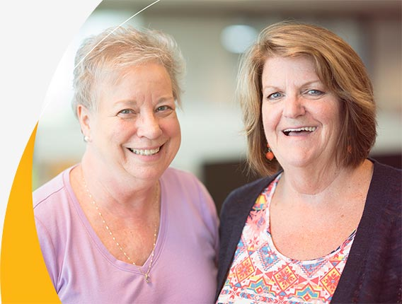 Two friendly, smiling women who are Gas South call center employees at the Atlanta-based office